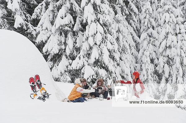 Österreich  Salzburg  Männer und Frauen am Kamin im Winter
