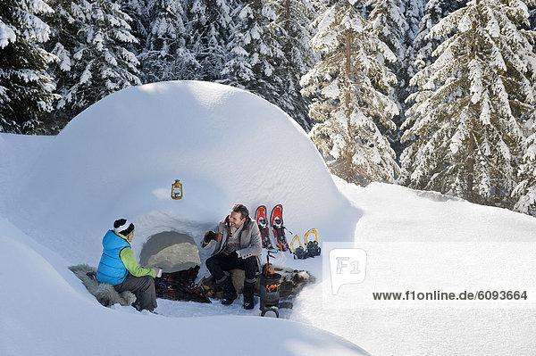 Austria  Salzburg County  Father and son sitting near igloo