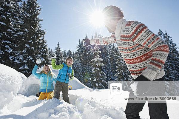 Austria  Salzburg County  Family playing near igloo