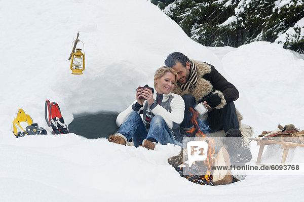 Austria  Salzburg County  Couple sitting near fireplace