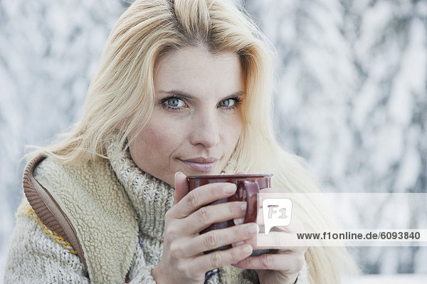 Österreich  Salzburger Land  Mittlere erwachsene Frau beim Tee trinken  lächelnd