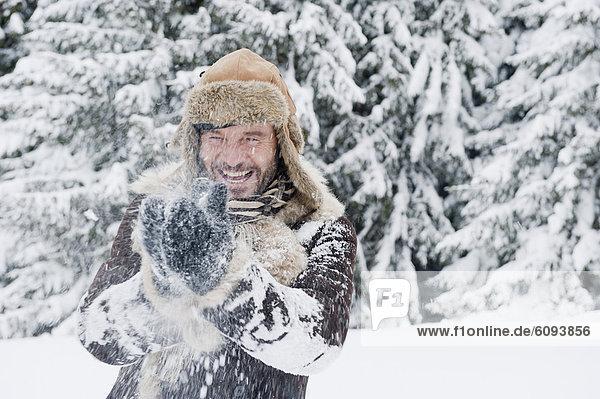 Austria  Salzburg County  Mature man having fun in snow  smiling