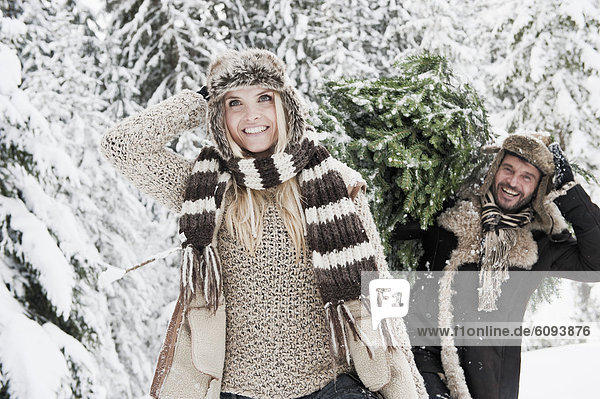 Austria  Salzburg County  Man and woman walking through snow while man carrying christmas tree