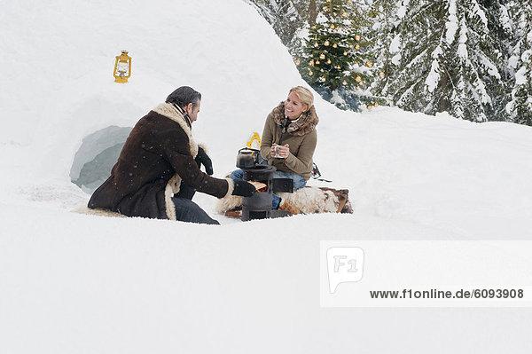 Österreich  Salzburger Land  Paar beim Campingkocher sitzend