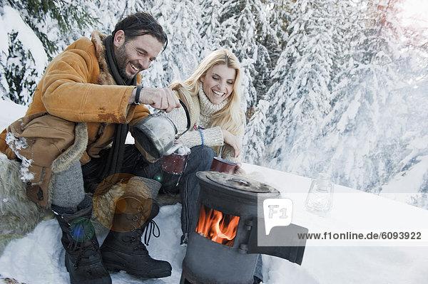 Österreich  Salzburger Land  Paar beim Campingkocher sitzend und Tee trinkend