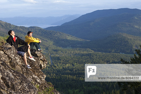 Two young men howl while enjoying the view after hiking in Idaho.