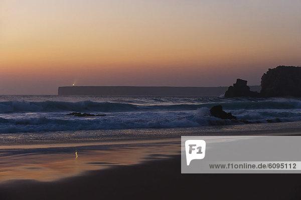 Portugal  Algarve  Sagres  Blick auf den Strand mit brechenden Wellen bei Sonnenuntergang