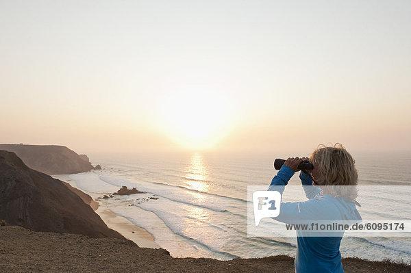 Portugal  Algarve  Sagres  Seniorin mit Blick auf den Strand durch ein Fernglas