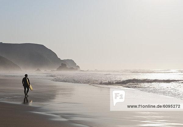 Portugal  Surfer walking on beach