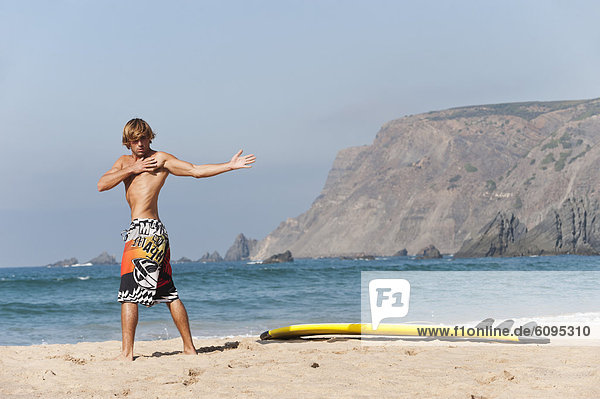 Portugal  Surfer standing by surfboard