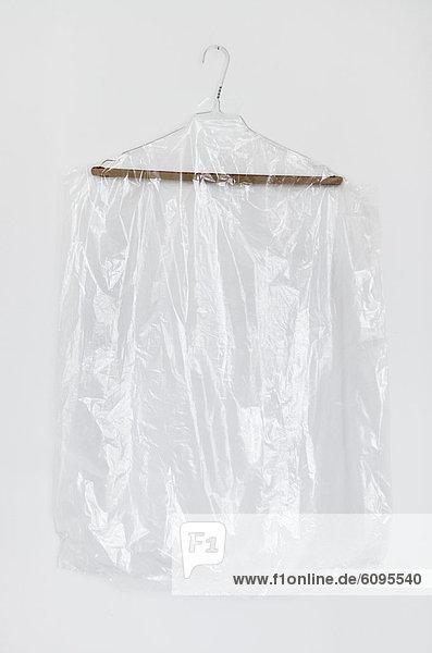 Plastikkleidung im Kleiderbügel auf weißem Hintergrund