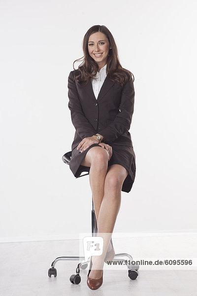 Geschäftsfrau auf Stuhl sitzend  lächelnd  Portrait