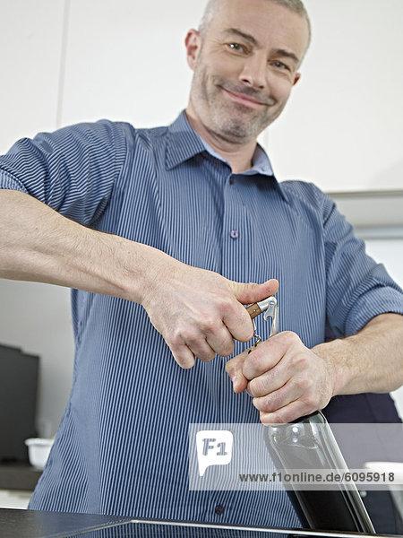 Reifer Mann öffnet Weinflasche  lächelnd  Portrait