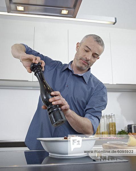 Reifer Mann beim Kochen in der Küche