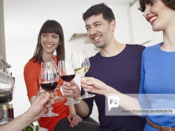 Männer und Frauen trinken Wein in der Küche