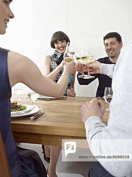 Männer und Frauen klirren an den Gläsern