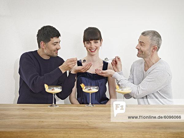 Männer füttern Dessert an Frau