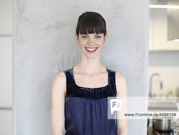 Mittlere erwachsene Frau in der Küche  lächelnd  Portrait