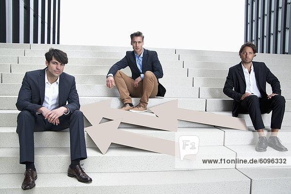 Deutschland  Nordrhein-Westfalen  Düsseldorf  Junge Geschäftsleute sitzen auf Treppen mit Pfeilen  Portrait
