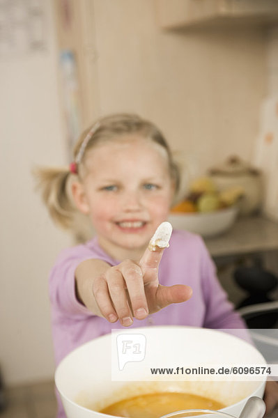 Girl showing finger covered with flour  smiling  portrait
