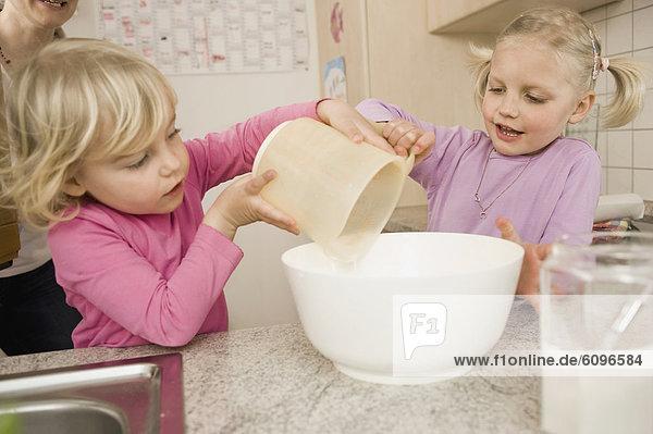 Schwestern machen Kuchen in der Küche