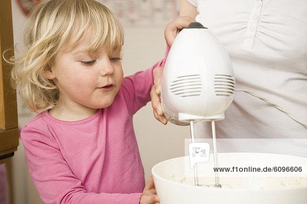Mutter und Tochter mischen Teig mit elektrischem Schneebesen Mutter und Tochter mischen Teig mit elektrischem Schneebesen
