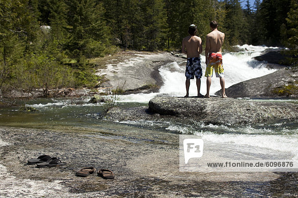 Two young men standing on a little island talk about jumping into the freezing river.