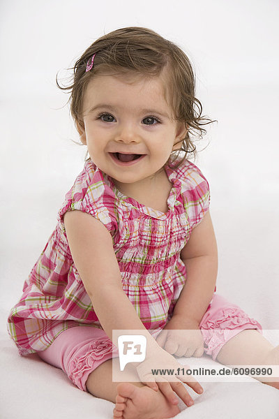 Baby girl sitting  smiling  portrait
