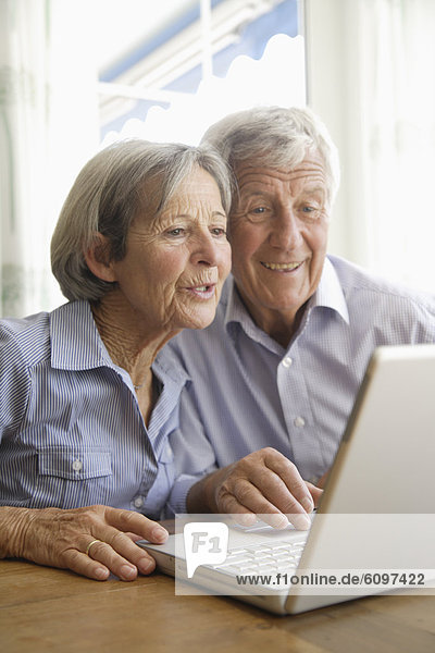 Germany  Bavaria  Senior couple using laptop at home