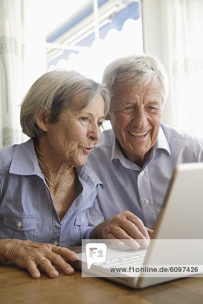 Deutschland  Bayern  Seniorenpaar mit Laptop zu Hause