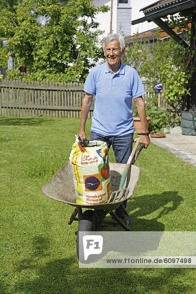 Senior mit Schubkarre im Garten
