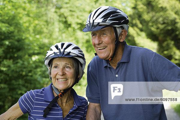 Germany  Bavaria  Senior couple with bicycle helmet  smiling