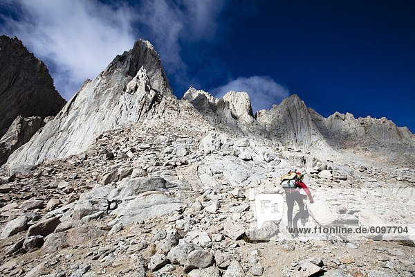 A female hiker scrambles up the mountaineer's route of Mount Whitney  California.