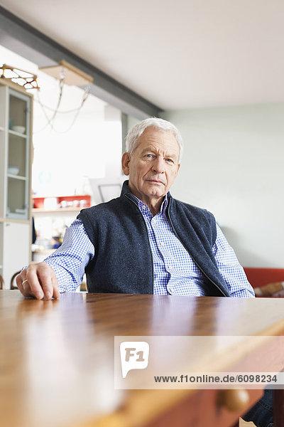 Älterer Mann am Tisch sitzend