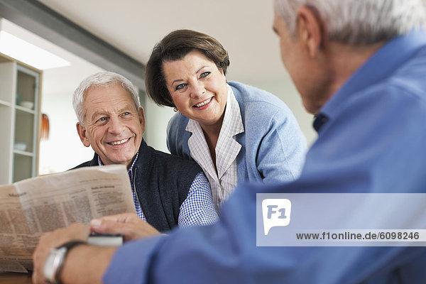 Senior Mann liest Zeitung  Mann und Frau lächeln