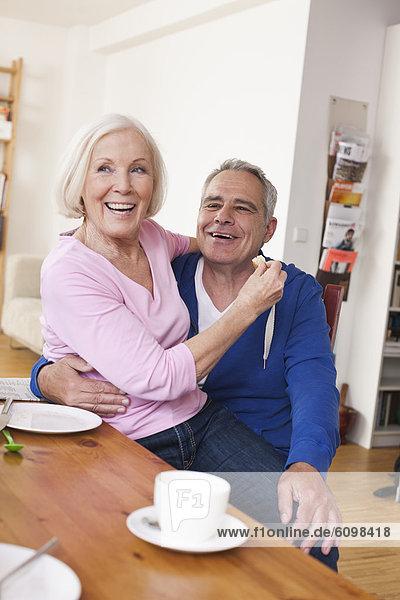Senior woman sitting on man's lap  smiling