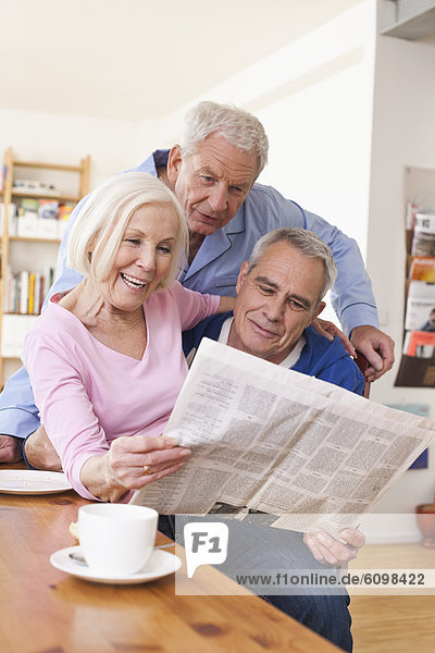 Senior men and woman reading newspaper  smiling