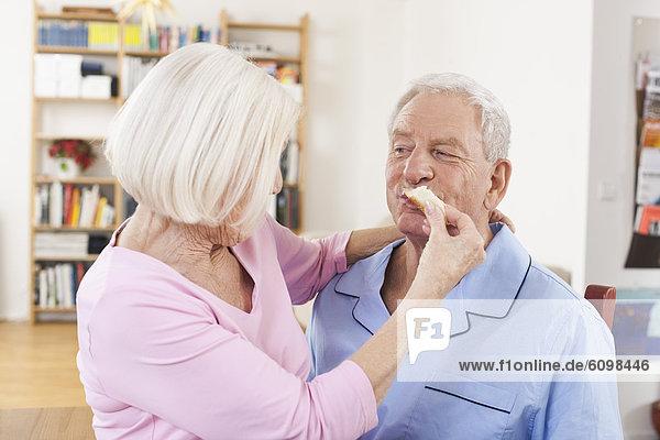 Seniorin füttert den Mann mit Käse