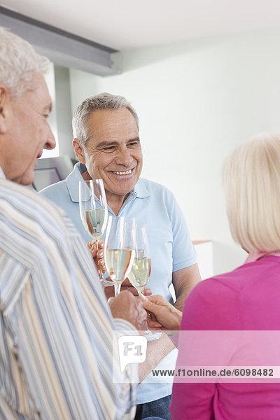 Senior men and women drinking sparkling wine  smiling