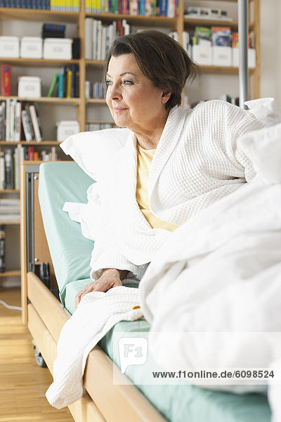 Senior woman getting up from medical bed