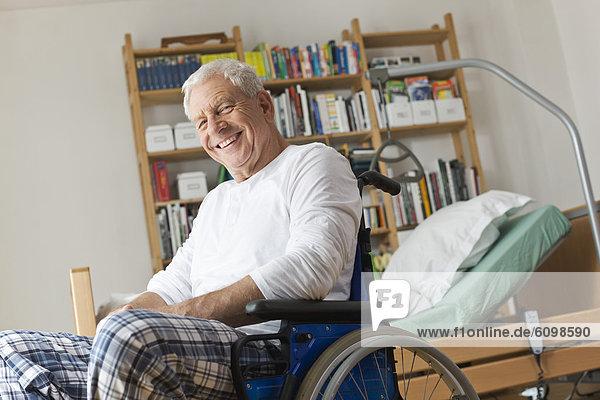 Senior man sitting on wheelchair  smiling