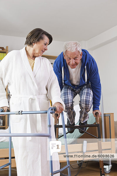 Senior man and woman with walking frame while man jumping