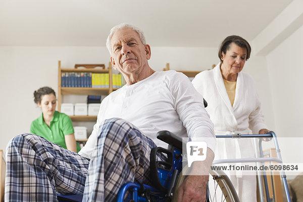 Älterer Mann auf Rollstuhl sitzend  Frau mit Gehgestell