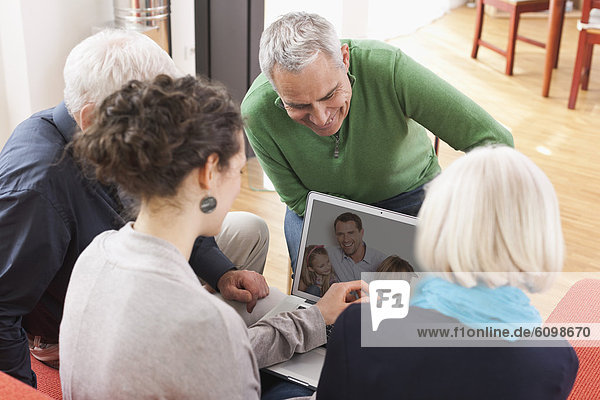Men and women watching pictures on laptop
