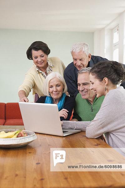 Männer und Frauen beim Betrachten von Bildern auf dem Laptop
