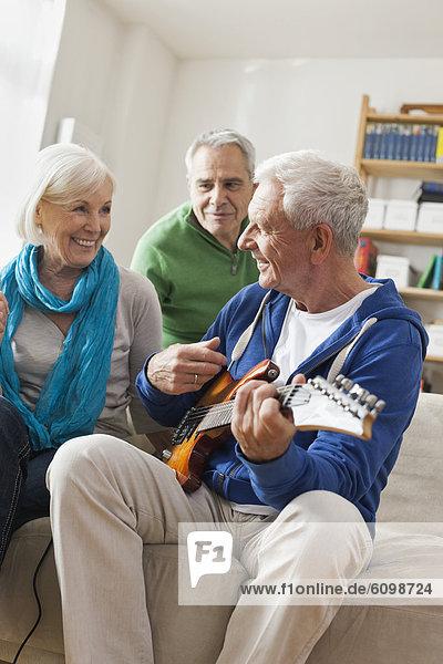 Senior man playing electric guitar,  man and woman sitting besides
