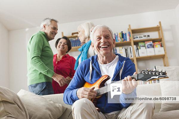 Senior Mann spielt E-Gitarre  Mann und Frau im Hintergrund