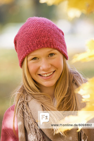 Austria  Close up of teenage girl with maple leaf  smiling