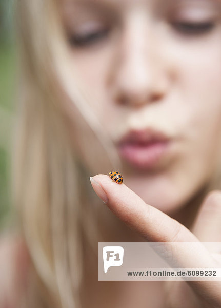 Österreich  Teenagermädchen schaut auf Marienkäfer am Finger