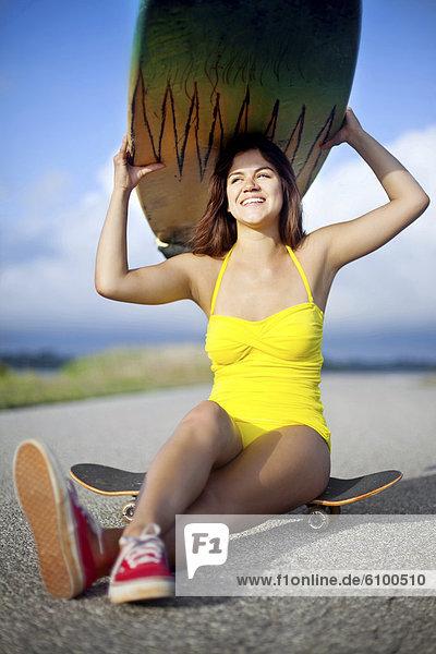 sitzend  Helligkeit  Frau  lächeln  Badeanzug  gelb  über  halten  Surfboard  Fernverkehrsstraße  Skateboard  jung  Kleidung